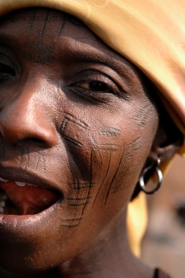 Benin, Abomey-Calavi December 02, 2006 - Woman with tribal scarification on her face. Scarification is used as a form of initiation into adulthood, beauty and a sign of a village, tribe, and clan. ©COSMOS / Jean-Michel Clajot